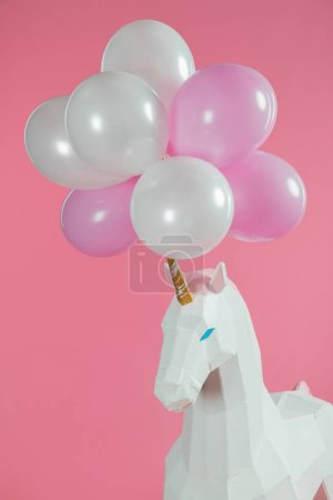 Bunch of air balloons on horn of toy unicorn isolated on pink