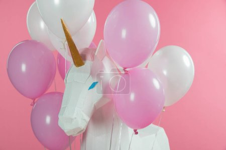 Magical unicorn with bunch of balloons isolated on pink