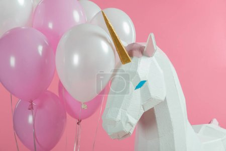 Bunch of balloons by party unicorn isolated on pink