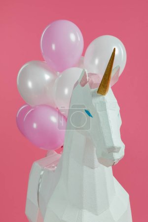 Paper unicorn with decorative air balloons isolated on pink