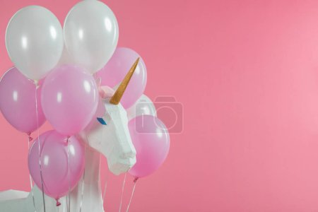 Toy unicorn among pink and white balloons isolated on pink