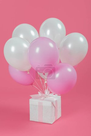 Presents with white and pink balloons on pink background