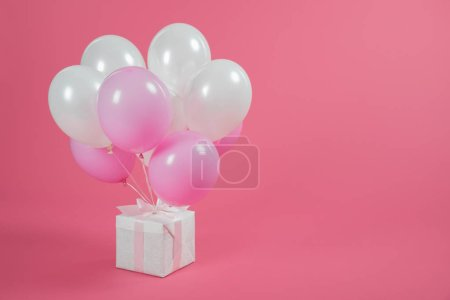 Photo for Gift box and balloons on pink background - Royalty Free Image