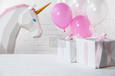 Decorative unicorn and balloons with gifts on white brick wall background