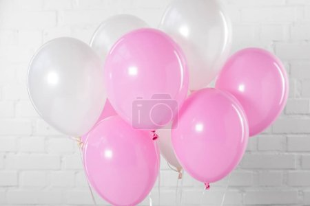 Pink and white party balloons on white brick wall background