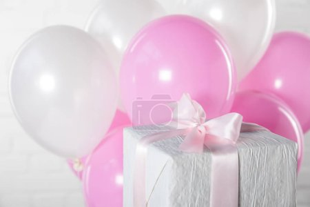 Gift box and balloons on white brick wall background