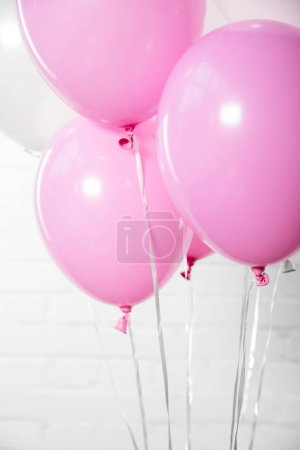 Shiny white and pink balloons on white brick wall background