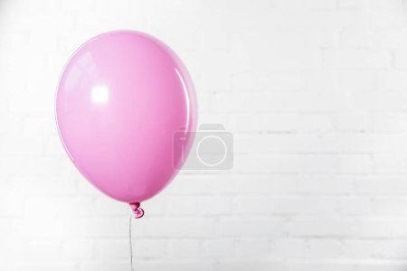 Single pink balloon on white brick wall background