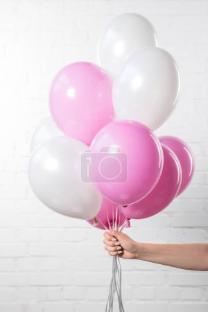 Female hand holding air balloons on white brick wall background