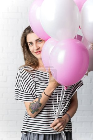Happy girl holding bunch of balloons on white brick wall background