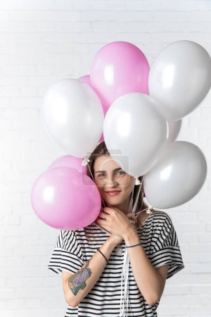 Smiling woman holding pink and white balloons on white brick wall background