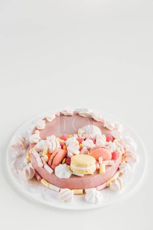 Photo for Pink cake with marshmallows and macarons on white plate with copy space - Royalty Free Image