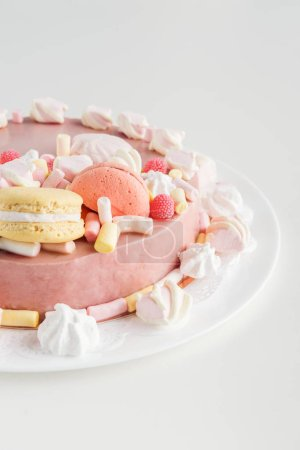 pink cake with buttercream, marshmallows and macarons on white plate