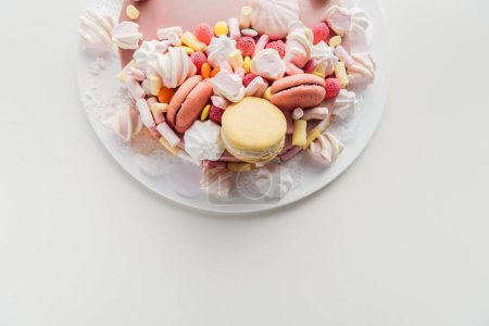 Photo for Top view of pink cake with marshmallows and macarons on white plate with copy space - Royalty Free Image
