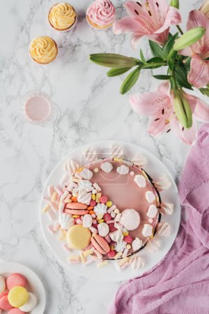 top view of sweet birthday cake with marshmallows and pink lily flowers on marble table
