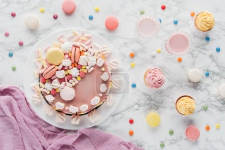 top view of pink birthday cake with marshmallows, cupcakes and milkshakes on marble table