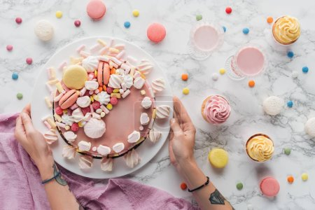 Photo for Cropped view of tattooed hands with pink birthday cake, candies, sweet cupcakes and milkshakes on marble table - Royalty Free Image