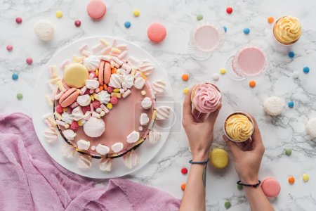 Photo for Cropped view of hands with cupcakes on table with pink birthday cake and milkshakes in glasses - Royalty Free Image