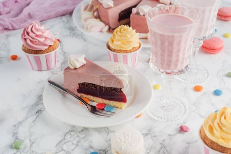piece of birthday cake, candies, sweet cupcakes and milkshake on marble table