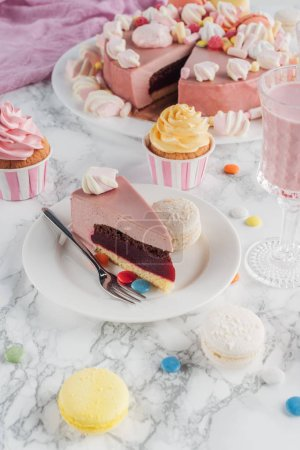 Photo for Piece of birthday cake, macaroons, colorful cupcakes and milkshake in glass on table - Royalty Free Image