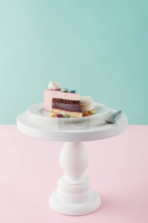 piece of cake with marshmallow and candies on plate with fork on cake stand