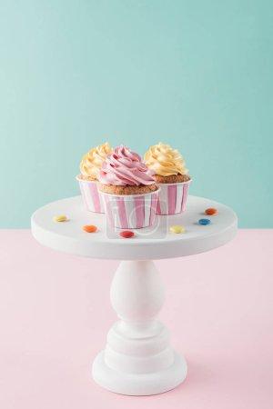 Photo pour Cupcakes avec la crème au beurre et les bonbons sur cake stand - image libre de droit