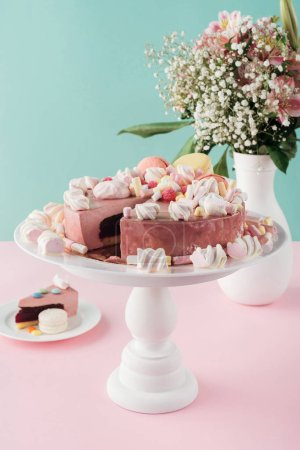 sweet cake with marshmallows and macarons on cake stand and bouquet of flowers in vase