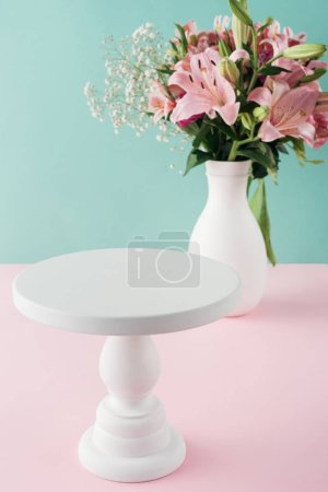 Photo for Empty white cake stand and bouquet of flowers in vase - Royalty Free Image