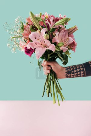 cropped view of tattooed male hand with bouquet of pink lily flowers