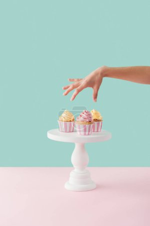 Photo for Cropped view of woman taking cupcakes from cake stand - Royalty Free Image