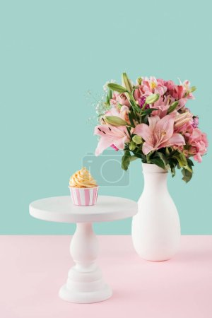 Photo pour Un cupcake sur le stand de gâteau et bouquet de fleurs de lis dans un vase - image libre de droit