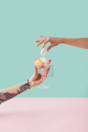Photo for Cropped view of woman taking of macaron from glass bowl in tattooed hand - Royalty Free Image