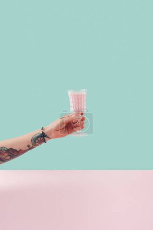 cropped view of female tattooed hand with glass of milkshake on pastel background