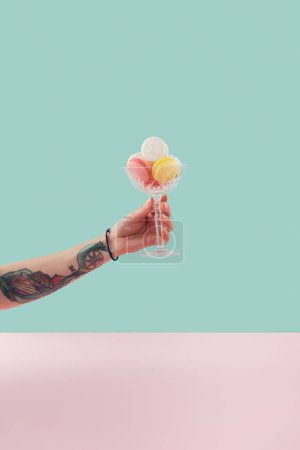 cropped view of tattooed hand with macarons in glass bowl on pastel background