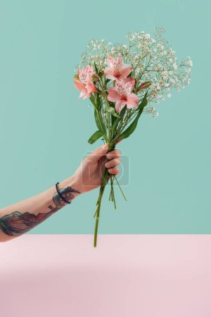 cropped view of tattooed woman holding bouquet with pink lily flowers