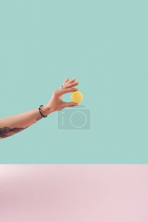 cropped view of tattooed hand with yellow macaron