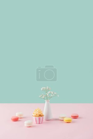 cupcake and sweet macarons on pastel background with flowers in vase