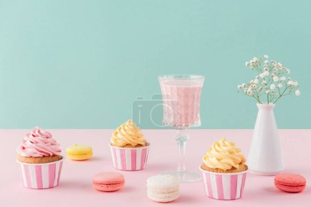 Photo for Cupcakes and sweet macarons and glass of milkshake on pastel background - Royalty Free Image