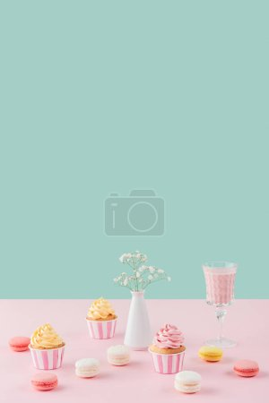 cupcakes, macarons, milkshake and flowers in vase on pastel background with copy space