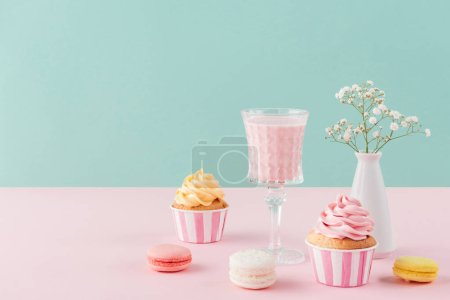 cupcakes, milkshake and macarons on birthday background with flowers