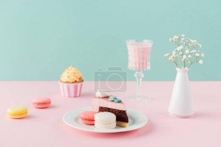 Photo pour Macarons, cupcake, morceau de gâteau et milkshake sur fond pastel - image libre de droit