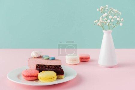 Photo pour Macarons et un morceau de gâteau sur plaque avec des fleurs dans un vase - image libre de droit