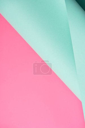 close-up view of bright turquoise and pink colored paper background