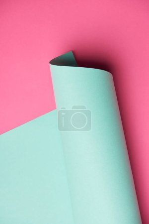 close-up view of rolled turquoise paper on pink background