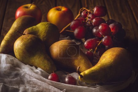 close-up shot of fresh grapes with pears and apples on cheesecloth