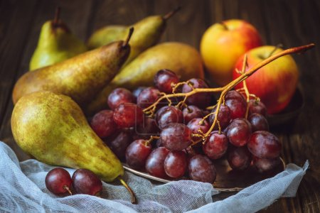 close-up shot of juicy grapes with pears and apples on cheesecloth