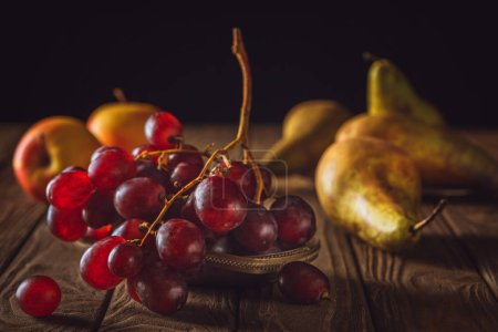 close-up shot of ripe pears and grapes on rustic wooden table on black