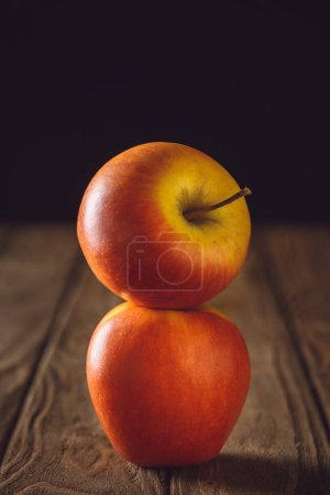 close-up shot of stacked red apples on rustic wooden table on black