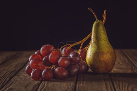 close-up shot of ripe pear and grapes on rustic wooden table on black