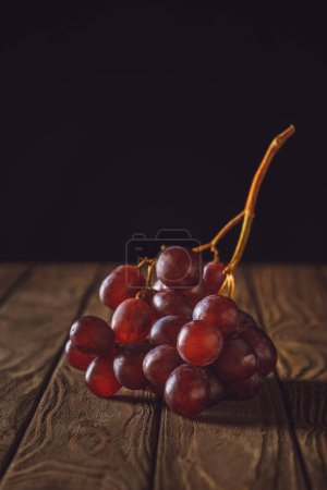 close-up shot of ripe red grapes on rustic wooden table on black